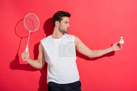 Photo pour Beau jeune homme tenant raquette de badminton et volant sur rose - image libre de droit
