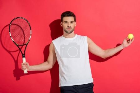 handsome young man holding tennis racket with ball and looking at camera on pink