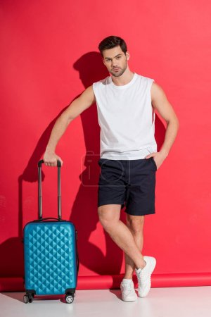 Photo for Handsome young man standing with suitcase and looking at camera on pink - Royalty Free Image