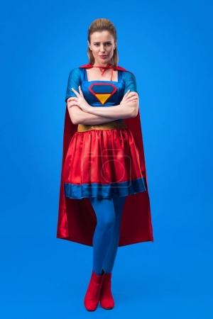 attractive woman in superhero costume with arms crossed isolated on blue