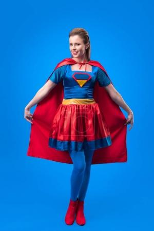 attractive woman in superhero costume holding cape isolated on blue