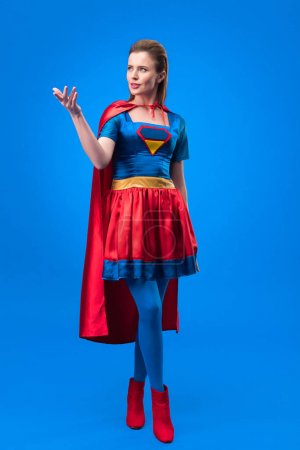 attractive woman in superhero costume with cape gesturing isolated on blue