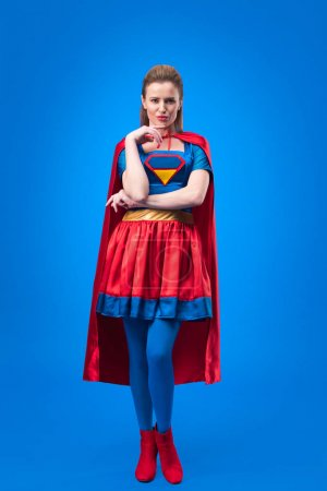 thoughtful woman in superhero costume looking at camera isolated on blue