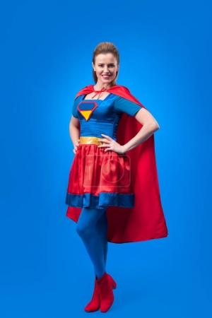 beautiful smiling woman in superhero costume standing akimbo isolated on blue