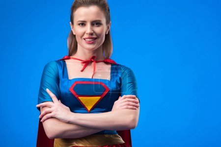 portrait of smiling woman in superhero costume with arms crossed isolated on blue