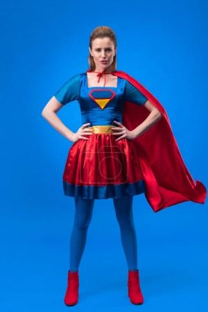 beautiful confident woman in superhero costume standing akimbo isolated on blue
