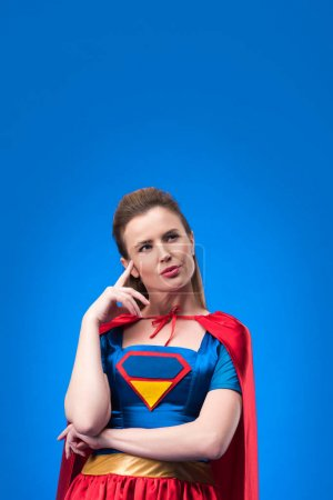 portrait of pensive woman in superhero costume looking away isolated on blue