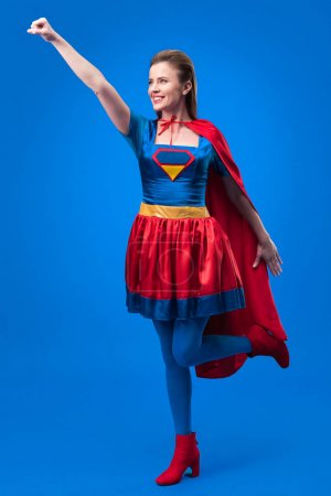 smiling woman in superhero costume with outstretched arm isolated on blue
