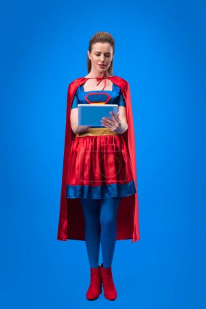 caucasian woman in superhero costume using tablet isolated on blue