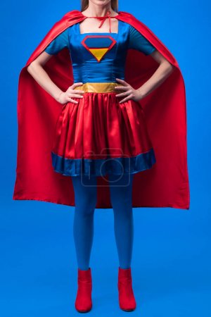 partial view of woman in superhero costume standing akimbo isolated on blue