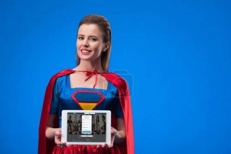 portrait of cheerful woman in superhero costume showing tablet isolated on blue