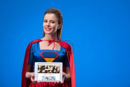 portrait of smiling woman in superhero costume showing tablet isolated on blue