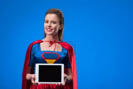 portrait of smiling woman in superhero costume showing tablet with blank screen isolated on blue