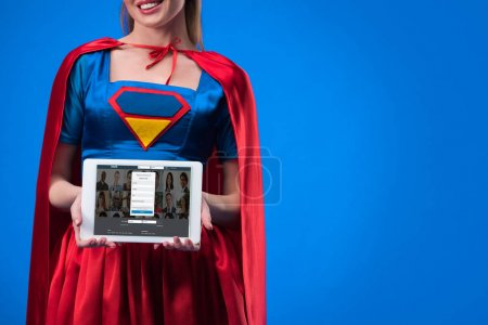 partial view of woman in superhero costume showing tablet isolated on blue