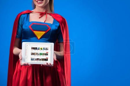 cropped shot of woman in superhero costume showing tablet isolated on blue