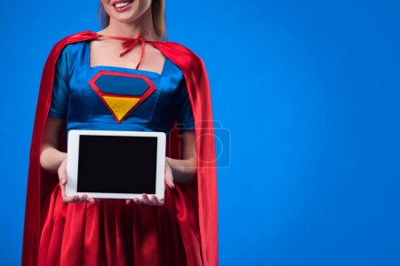 partial view of woman in superhero costume showing tablet with blank screen isolated on blue