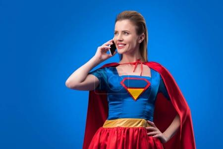 portrait of smiling woman in superhero costume talking on smartphone isolated on blue