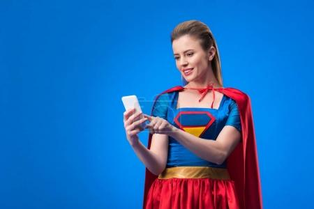 portrait of smiling woman in superhero costume using smartphone isolated on blue