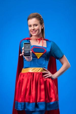 portrait of smiling woman in superhero costume showing smartphone isolated on blue