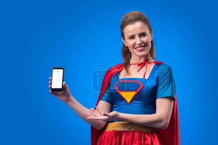 Photo for Portrait of smiling woman in superhero costume showing smartphone isolated on blue - Royalty Free Image