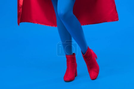 partial view of woman in superhero costume isolated on blue