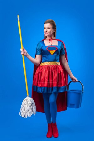 attractive woman in superhero costume with mop and bucket for cleaning isolated on blue