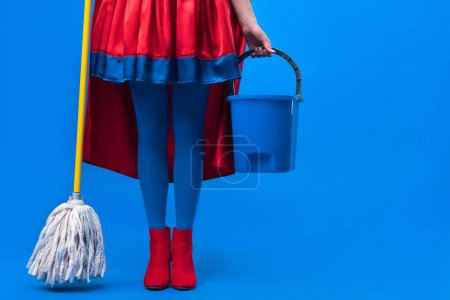 partial view of woman in superhero costume with mop and bucket for cleaning isolated on blue