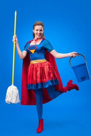 happy woman in superhero costume with mop and bucket for cleaning isolated on blue