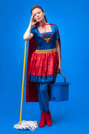 tired woman in superhero costume with mop and bucket for cleaning isolated on blue