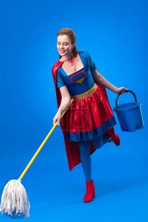 smiling woman in superhero costume with mop and bucket for cleaning isolated on blue