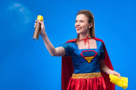 portrait of beautiful smiling superwoman with rag and detergent for cleaning isolated on blue