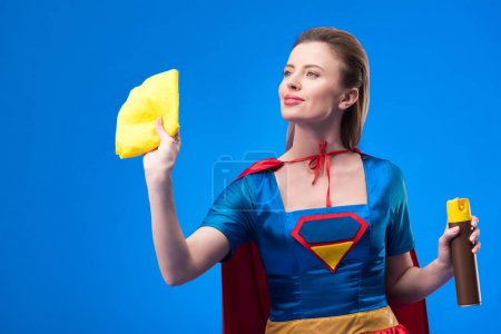 portrait of beautiful superwoman with rag and detergent for cleaning isolated on blue