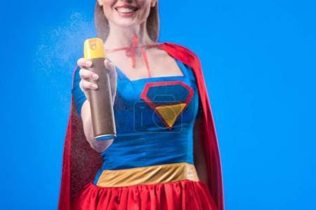 partial view of smiling superwoman with detergent in hand isolated on blue