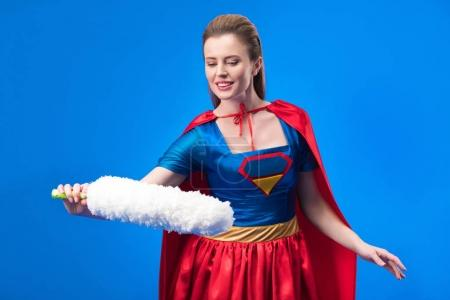 portrait of smiling woman in superhero costume with dust cleaning brush isolated on blue