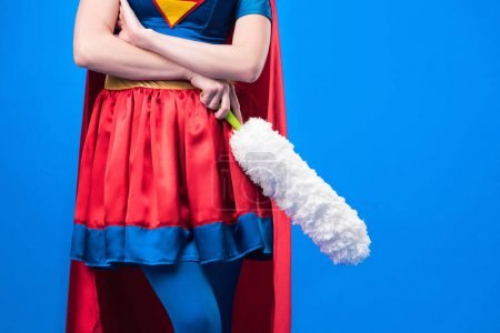 cropped shot of woman in superhero costume with dust cleaning brush isolated on blue