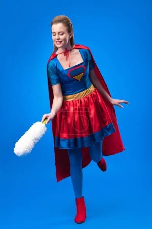 smiling woman in superhero costume with dust cleaning brush isolated on blue