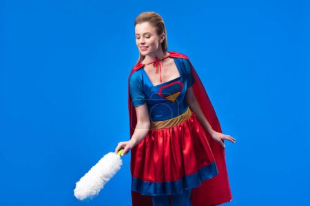portrait of woman in superhero costume with dust cleaning brush isolated on blue