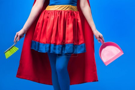 partial view of woman in superhero costume with broom and scoop for cleaning isolated on blue