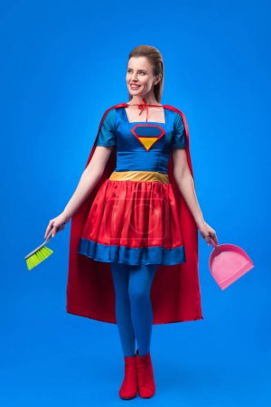 woman in superhero costume with broom and scoop for cleaning isolated on blue