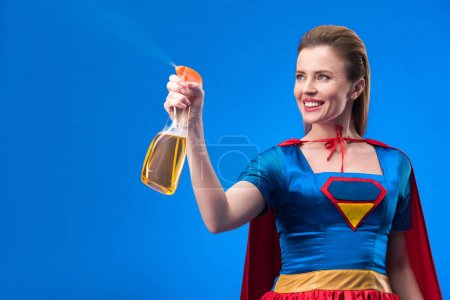 portrait of cheerful superwoman with detergent in hand isolated on blue