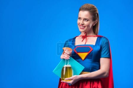 portrait of smiling woman in superhero costume with rag and detergent in hands isolated on blue