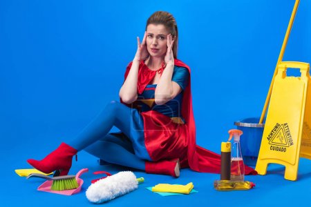 tired woman in superhero costume with cleaning supplies around isolated on blue