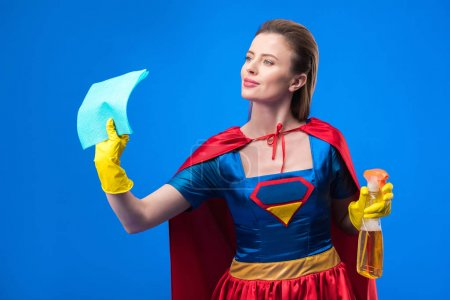 portrait of woman in superhero costume and rubber gloves with rag and detergent isolated on blue