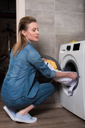 Photo for Housewife taking out laundry from washing machine at home - Royalty Free Image