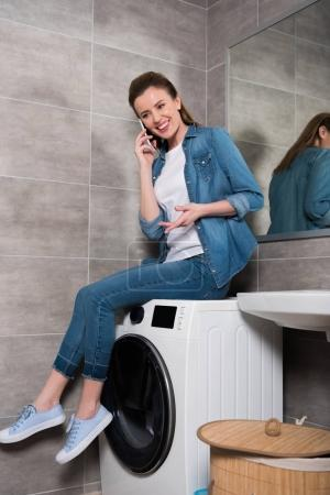 Photo for Cheerful housewife talking on smartphone while sitting on washing machine at home - Royalty Free Image