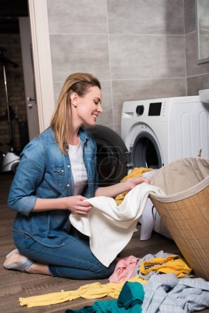 Photo for Smiling housewife taking clothing to put it into washing machine at home - Royalty Free Image