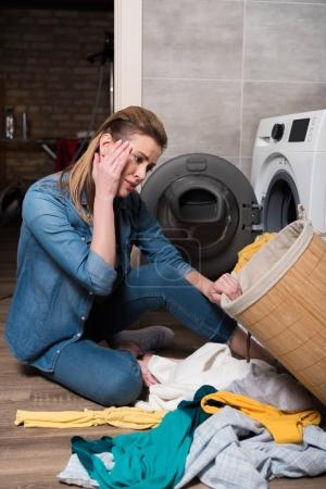 emotional housewife looking at clothing before putting it into washing machine at home