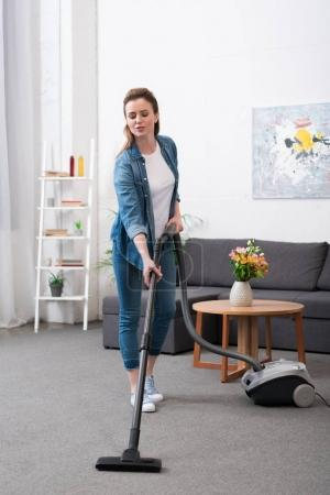 Photo for Attractive woman with vacuum cleaner cleaning room at home - Royalty Free Image