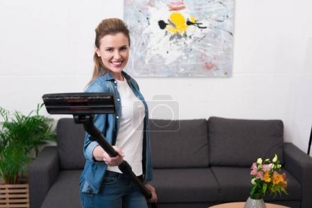 Photo for Portrait of cheerful woman holding vacuum cleaner in hands at home - Royalty Free Image