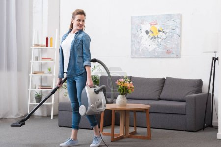 smiling woman with vacuum cleaner in hands looking away